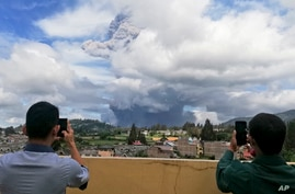 Men use their mobile phones to take photos as Mount Sinabung spews volcanic materials into the air as it erupts, in Karo, North Sumatra, Indonesia, Aug. 10, 2020.