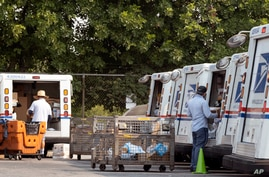 Postal workers load packages in their mail delivery vehicles in the Panorama City section of Los Angeles, California, Aug. 20, 2020.