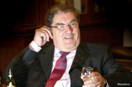 FILE - Former Social Democratic and Labour Party (SDLP) leader John Hume sits with a drink after announcing at a news conference in Belfast, that he will not be standing again for the European Parliament, Feb. 4, 2004.