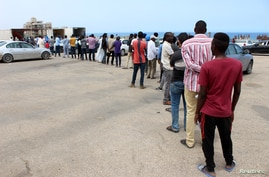 FILE - Migrants queue to receive food aid distributed by UNHCR amid the coronavirus pandemic, in Tripoli, Libya, May 12, 2020. The IOM has repatriated more than 100 Ghanaian migrants due to the ongoing conflict and virus spread in Libya.
