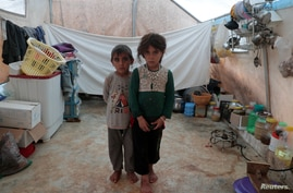 FILE - Syrian siblings, displaced from eastern Idlib province, pose for a picture in a tent at Atmeh camp in Syria, near the Turkish border, June 19, 2020.