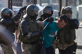 Belarusian law enforcement officers detain a man during a rally following the presidential election in Minsk, Aug. 11, 2020.