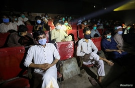 People wear protective masks while watching a movie at a cinema in Peshawar after Pakistan lifted lockdown restrictions, as the coronavirus disease (COVID-19) outbreak continues, Aug. 10, 2020.