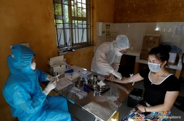 Medical specialists collect blood sample from a woman who has returned after travelling to Da Nang, at a rapid testing center for COVID-19 outside Hanoi, Vietnam, July 30, 2020.
