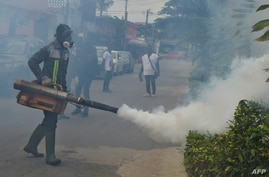 Officers of the National institute for public hygiene (INHP) are at work to fumigate an area to prevent mosquitos from breeding…