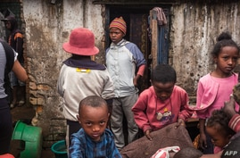 Residents of Anjezika, one of Antananarivo's poorest and most unhealthy neighbourhoods, stand around on May 13, 2020. - Le…