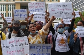 Supporters of Rong Chhun, leader of the Cambodian Confederation of Unions hold placards during a protest in front of Phnom Penh…