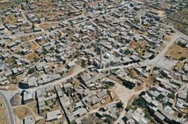 An aerial view shows the deserted village of Kansafra in Jabal al-Zawiya region of Syria's northwestern province of Idlib on…