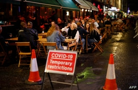 People drink at the outside tables of a cafe in Soho, in central London on September 23, 2020. - Britain on Tuesday tightened…