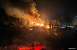 FILE - A fire burns at the migrant camp on the island of Samos, Greece, April 26, 2020.