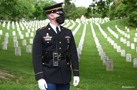 A U.S. Army soldier stands guard in front of rows of graves as U.S. President Donald Trump visits Arlington Nat. Cemetery.