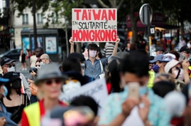 """A man wearing a protective mask holds a placard reading: """"Taiwan in solidarity with Hong Kong"""" as people demonstrate in support…"""