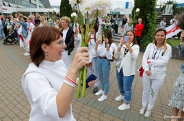 Representative of the Coordination Council for members of the Belarusian opposition Olga Kovalkova holds flowers as she attends…