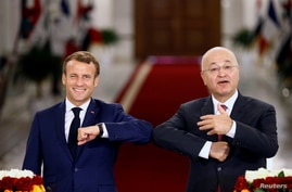 French President Emmanuel Macron and Iraq's President Barham Salihat greet each other with an elbow bump as they attend a news…
