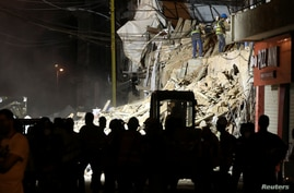 Volunteers dig through the rubble of buildings which collapsed by the explosion at the city's port area, after signs of life…