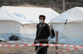 A man wearing a protective face mask walks at a new temporary camp for migrants and refugees, on the island of Lesbos, Greece,…