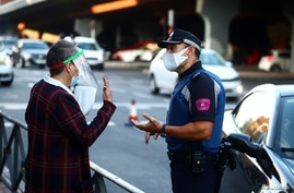 A local police officer speaks with a woman in the Vallecas neighbourhood during the first day of a partial lockdown between and…