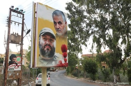A poster depicting assassinated Hezbollah military commander Imad Moughniyeh and the late Iran's Quds Force top commander…