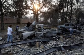 Maria Arevalo, left, and her husband Antonio Silva search for items to salvage in the remains of their burned home, in a…