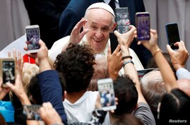 Pope Francis greets faithful as he arrives at the San Damaso courtyard for the weekly general audience at the Vatican,…