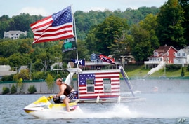 A jet skier passes a patriotic shanty-boat owned by AJ Crea on Pontoosuc Lake on Labor Day in Pittsfield, Mass.