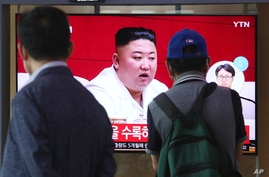 People watch a screen showing a file image of North Korean leader Kim Jong Un during a news program at the Seoul Railway.