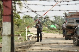 A Myanmar police officer stands watch as journalists arrive in Shwe Zar village in the suburb of Maungdaw town, northern Rakhine state of Myanmar, on Wednesday, Sept. 6, 2017.