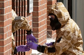 FILE - In this Friday, July 6, 2018 file photo specialist team members in military protective suits during Novichok  nerve…