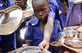 In this photo taken Tuesday, March 26, 2019, children push their plates out to receive a portion of cooked grains during a…