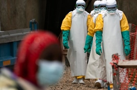 FILE - In this Tuesday, July 16, 2019 file photo, health workers dressed in protective gear begin their shift at an Ebola…