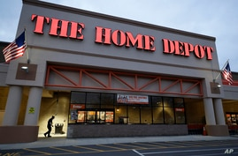 In this Monday, Jan. 27, 2020 photo a passer-by, below left, walks toward an entrance to a Home Depot store location, in Boston…
