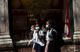 Children wear protective face masks as they walk in the historical center of Brussels, Wednesday, Aug. 12, 2020. Authorities in…