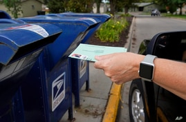 FILE - In this Tuesday, Aug. 18, 2020, file photo, a person drops applications for mail-in-ballots into a mail box in Omaha,…