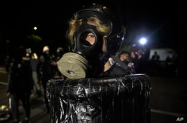 A protester wearing a gas mask is seen during the nightly protests at a Portland police precinct on Sunday, Aug. 30, 2020 in…