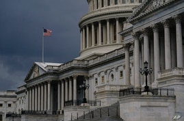 FILE - In this Aug. 3, 2020, file photo dark clouds and heavy rain sweep over the U.S. Capitol in Washington. The federal…