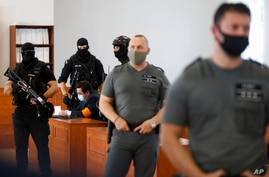 Marian Kocner is surrounded by armed police officers in the courtroom after a trial against him in Pezinok, Slovakia, Sept. 3, 2020.