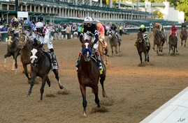 Jockey John Velazquez riding Authentic (18) crosses the finish line to win the 146th running of the Kentucky Derby at Churchill…