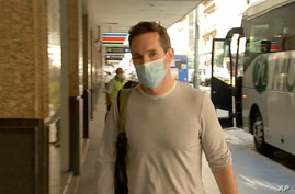 Australian Broadcasting Corp. journalist Bill Birtles walks into a hotel for quarantine in Sydney, Australia, Sept. 8.