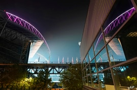 Smoke from wildfires is seen in the air as lights from T-Mobile Park, left, are reflected in a window of CenturyLink Field,…