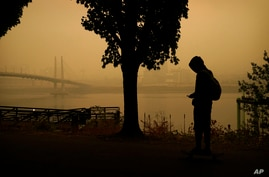 A person rides a skateboard along the Willamette River as smoke from wildfires partially obscures the Tilikum Crossing Bridge,…