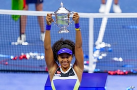 Naomi Osaka, of Japan, holds up the championship trophy after defeating Victoria Azarenka, of Belarus, in the women's singles…