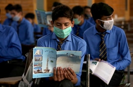 Students wearing face masks to prevent the spread of coronavirus, attend their class at a school, in Peshawar, Pakistan, Sept. 15, 2020.