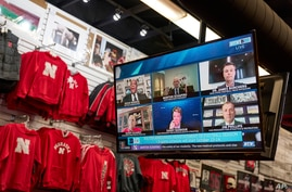 The Husker Hounds sports apparel store in Omaha, Neb., shows on television screens Wednesday, Sept. 16, 2020, a Big Ten virtual…