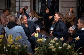 FILE - In this Wednesday, April 8, 2020 file photo people chat and drink outside a bar in Stockholm, Sweden. Sweden's…