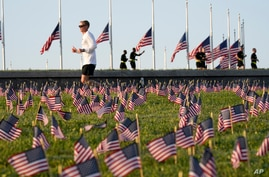 Morning joggers look over small flags that activists from the COVID Memorial Project placed on the grounds of the National Mall
