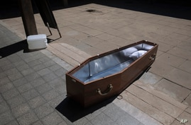 An open coffin lies on the ground at a special morgue for COVID-19 victims in the central Israeli city of Holon, near Tel Aviv,…