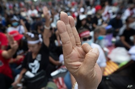Pro-democracy demonstrators raise a three-finger salute, a symbol of resistance, during a protest outside the Parliament in…
