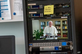 Pope Francis is seen on a video screen at United Nations headquarters as he speaks in a pre-recorded message addressing the…