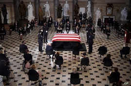 A U.S. Capitol Police honor guard surrounds the flag-draped casket of Justice Ruth Bader Ginsburg as lies in state.