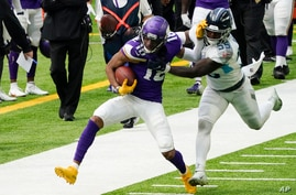 Minnesota Vikings wide receiver Justin Jefferson (18) tries to break a tackle by Tennessee Titans inside linebacker Jayon Brown…